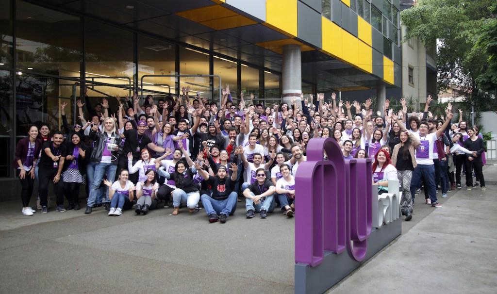 Como é ser engenheira do Nubank: muitas pessoas do Nubank em frente ao escritório com os braços levantados em comemoração.