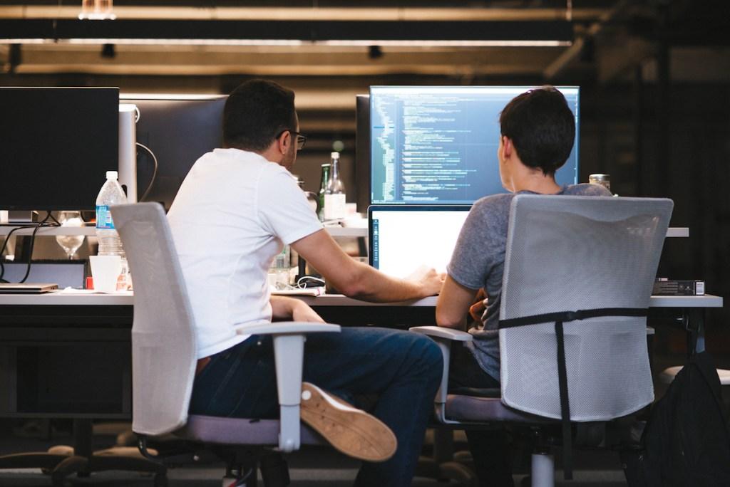 Dois homens sentados, trabalhando juntos num computador e um código de programação na tela.