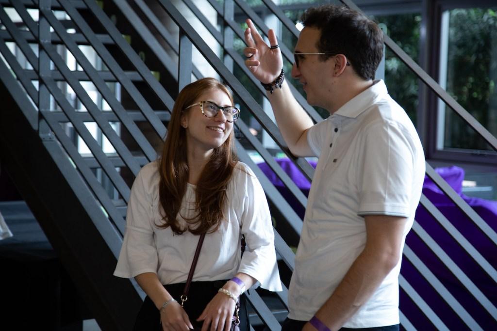 Dois estudantes conversando ao pé da escada no escritório do Nubank.