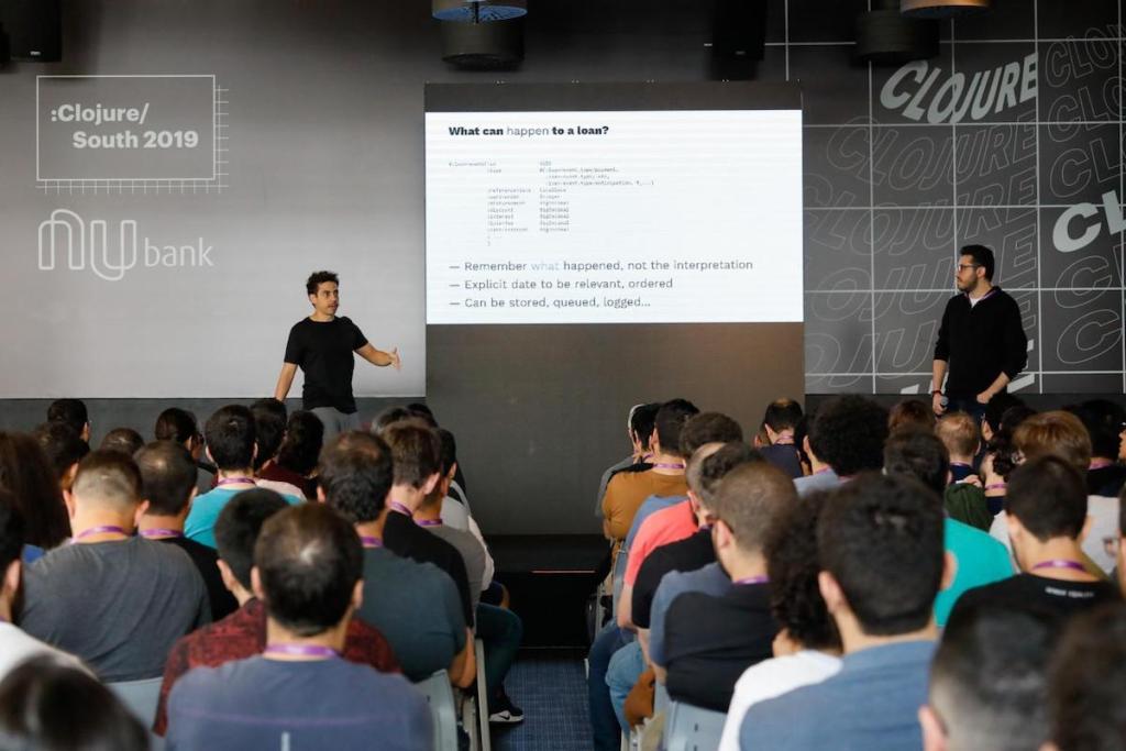 Dois homens apresentando para uma plateia no evento Clojure South 2019.