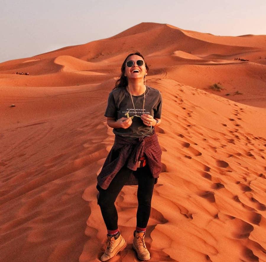Mulher sorrindo em frente a dunas do deserto