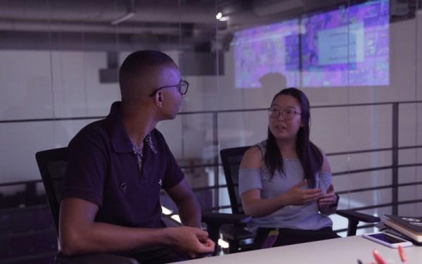 Ramon conversando com uma Nubanker. Ela está de blusa roxa e ela com uma blusa de manga curta clara e óculos.