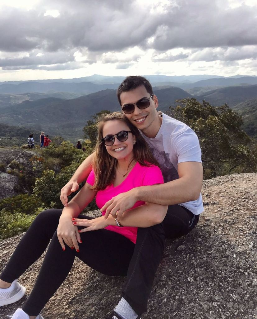 Morar Junto: fotografia de Rafael e Luana sentados abraçados em uma pedra, no alto da montanha, com uma bela vista atrás.