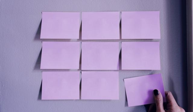 MVP: imagem de 9 post its roxos em grupos de 3 colados em uma parede, com uma mão retirando o mais abaixo