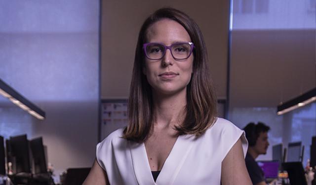 Imagem de uma mulher sentada, olhando para a câmera. Ela veste uma camiseta branca e usa óculos