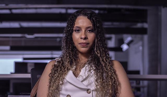 Imagem de uma mulher sentada, olhando para a câmera. Ela veste uma blusa branca e tem o cabelo cacheado