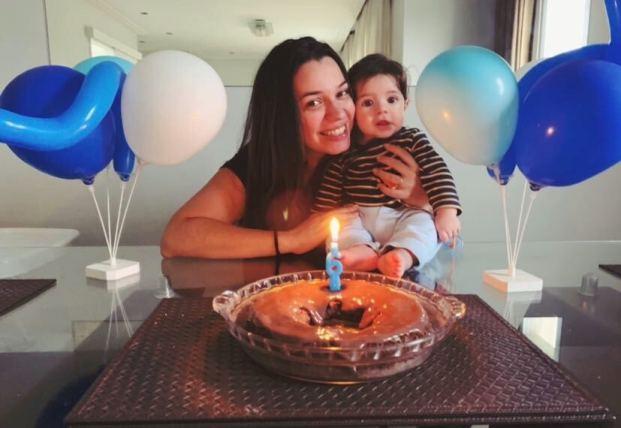 Thamyris abraçando seu filho Gabriel, em frente a um bolo em comemoração aos 6 meses dele.