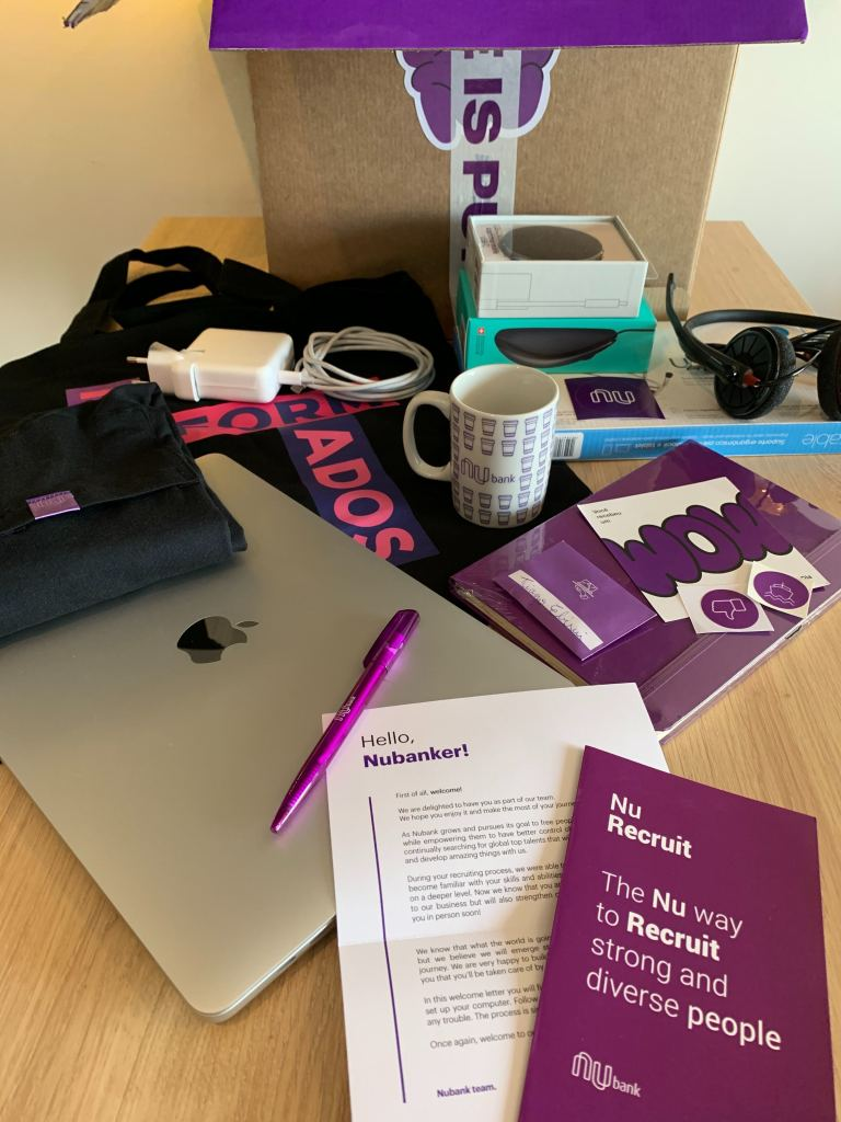 Nubank welcome kit: a computer and purple items, such as a pen, a letter and mug.