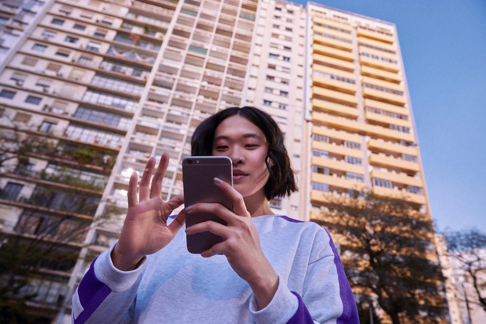 imagem de uma mulher de cabelo curto, em frente a um prédio, segurando um celular.