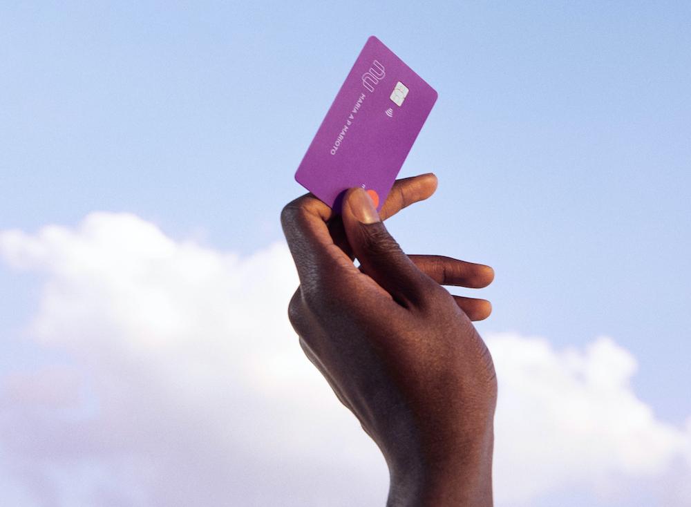 Imagem da mão de uma pessoa segurando um cartão de crédito Nubank no ar