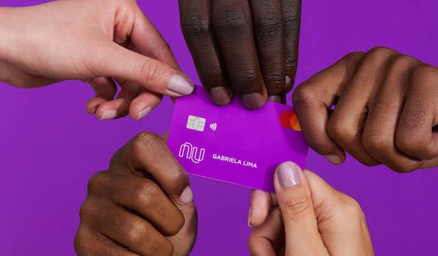 no fundo roxo, cinco mãos seguram o cartão Nubank