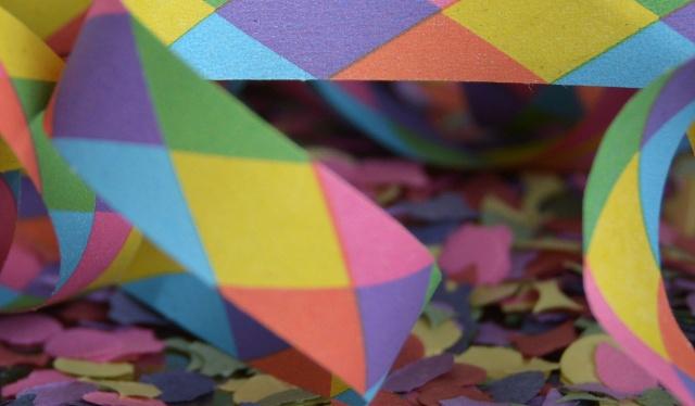 Foto de uma serpentin colorida em cima de confete picado
