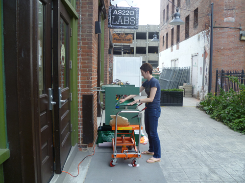 Ruth learning how to vacuum-mould masks designed by Foo Fest artist in residence Xander Marro outside AS220 Industries.