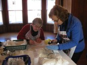 Conservation volunteers at Highwic cleaning glass objects.