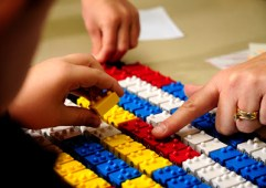 child and teacher playing with braille logo blocks