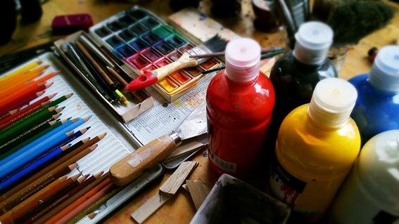 mesa de trabalho com várias tintas, pinceis, lápis, espátulas e aguarela