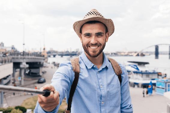 rapaz jovem de camisa zul, chapéu e mochila a tirar fotografias com um selfie stick num porto
