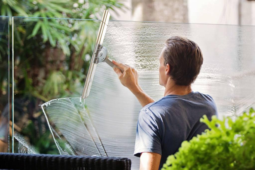 Homem jovem a limpar vidrios