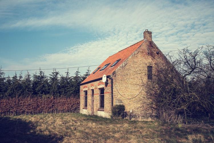 Casa abandonada rodeada de terreno com muito mato