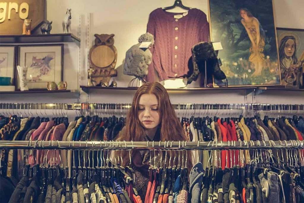 Mulher à procura de roupas vintage na loja