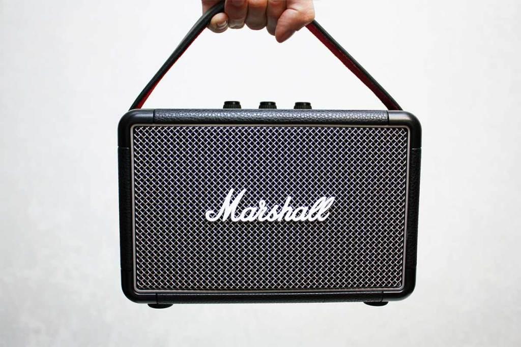 Mão a segurar uma coluna portátil da Marshall