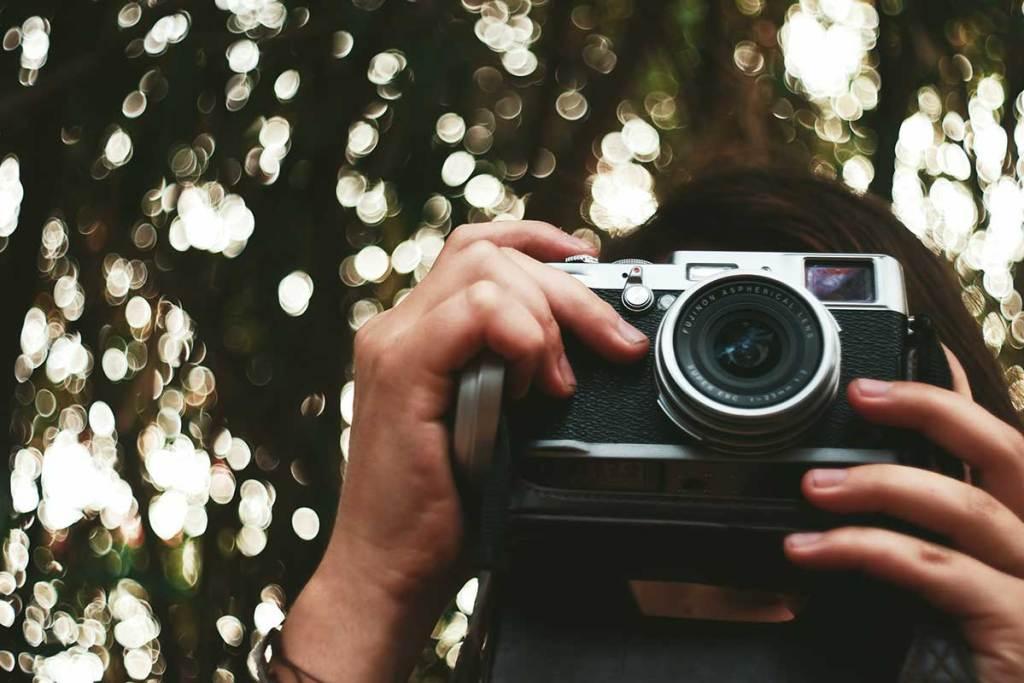Mulher jovem a tirar fotografia com uma máquina analógica