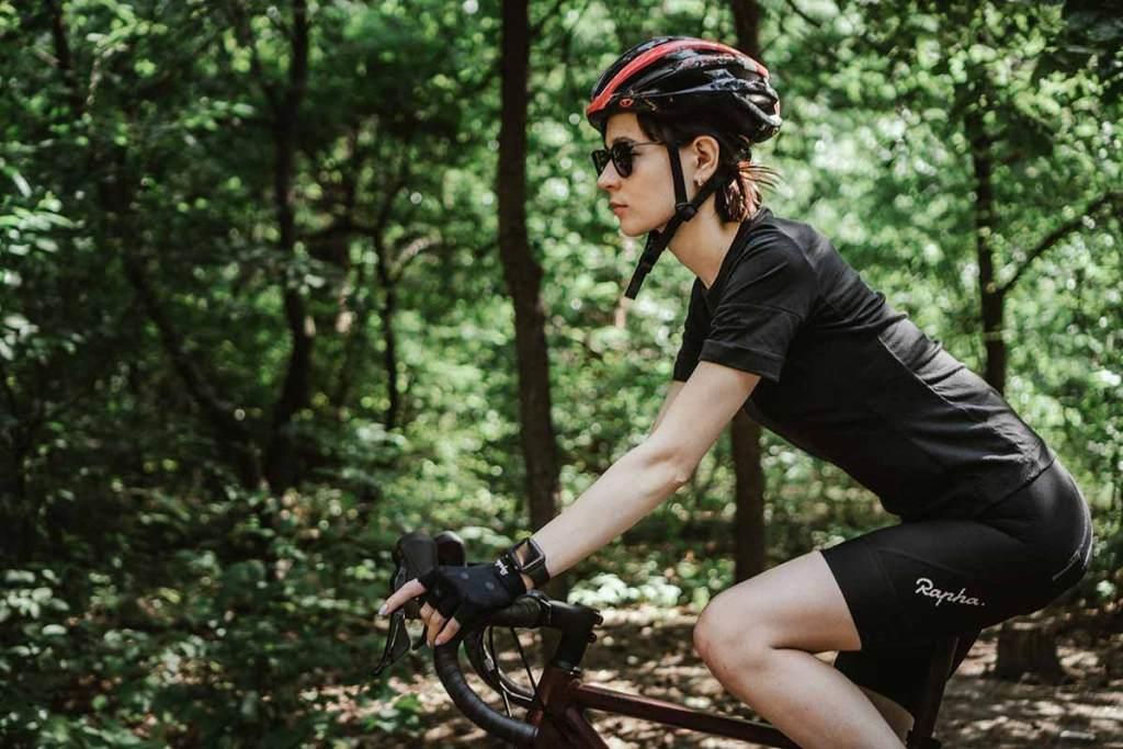 Mulher com capacete e luvas de bicicleta