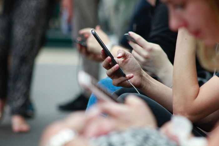 A photo of people using mobile phones.