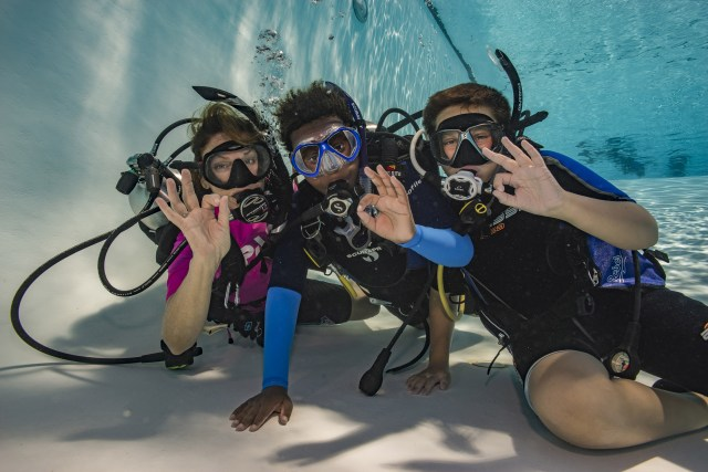 Kids learning to scuba dive in a pool