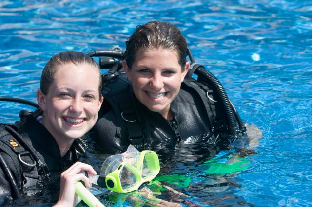 Two female divers smile nex tto each other