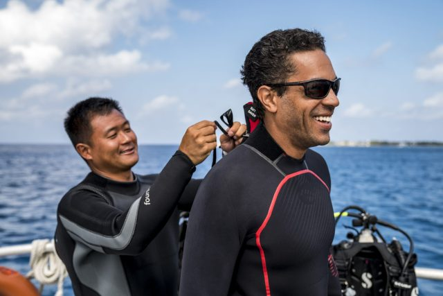 Diver assists another diver with his wetsuit