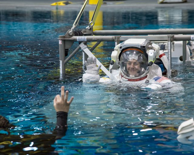 A female astronaut in a EVA suit smiles and waves to a scuba diver