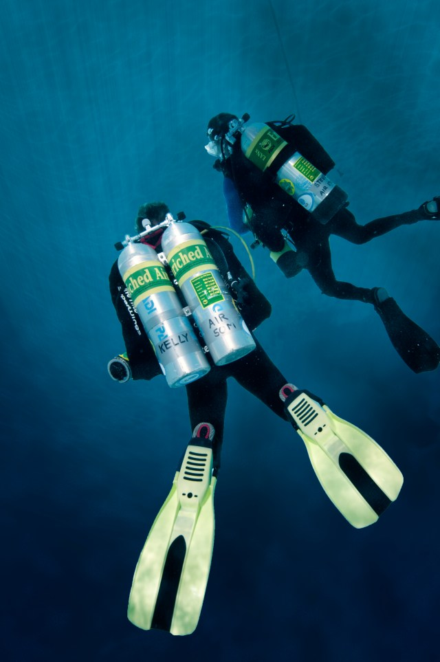 a diver wearing two tanks on her back aka doubles