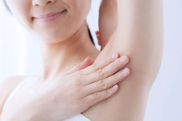 woman touching armpit