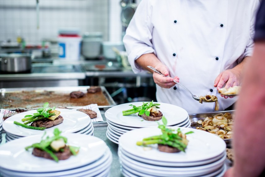Chef spooning food onto plate