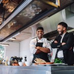 Restaurant labor cost: Smiling restaurant owner and chef standing in kitchen