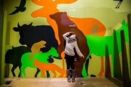 Enfant se mesurant pour se comparer avec les animaux dans l'exposition Crapahut'