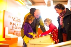 Famille découvrant les différents matériaux dans l'exposition Matéri'Oh
