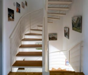 Staircase inside the first Passive House with various paintings on the wall