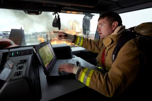 A uniformed firefighter inside a firetruck using a Dell Latitude 14 7404 Rugged Extreme Notebook to determine extent of fire damage.