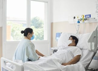 Woman Visiting Male Patient in Hospital Ward