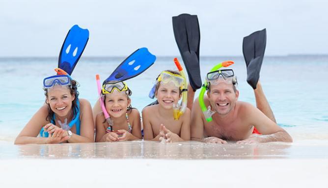 Gezin ligt op het strand met zwemvliezen en duikbrillen op sterktes