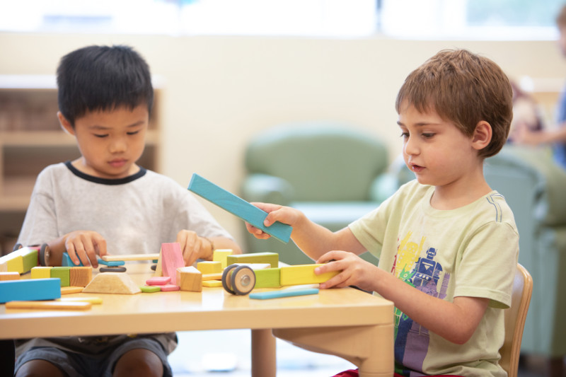 Two young boys playing with blocks at a table