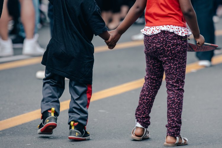 Two kids crossing the street, holding hands