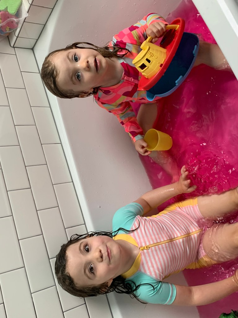 A young girl wearing a pink and aqua striped swimsuit sits in a bathtub filled with bright pink water. Her younger sister sits to her left in a pink and orange camouflage print bathing suit while holding a yellow cup and plastic yellow, orange, and black tugboat bath toy.