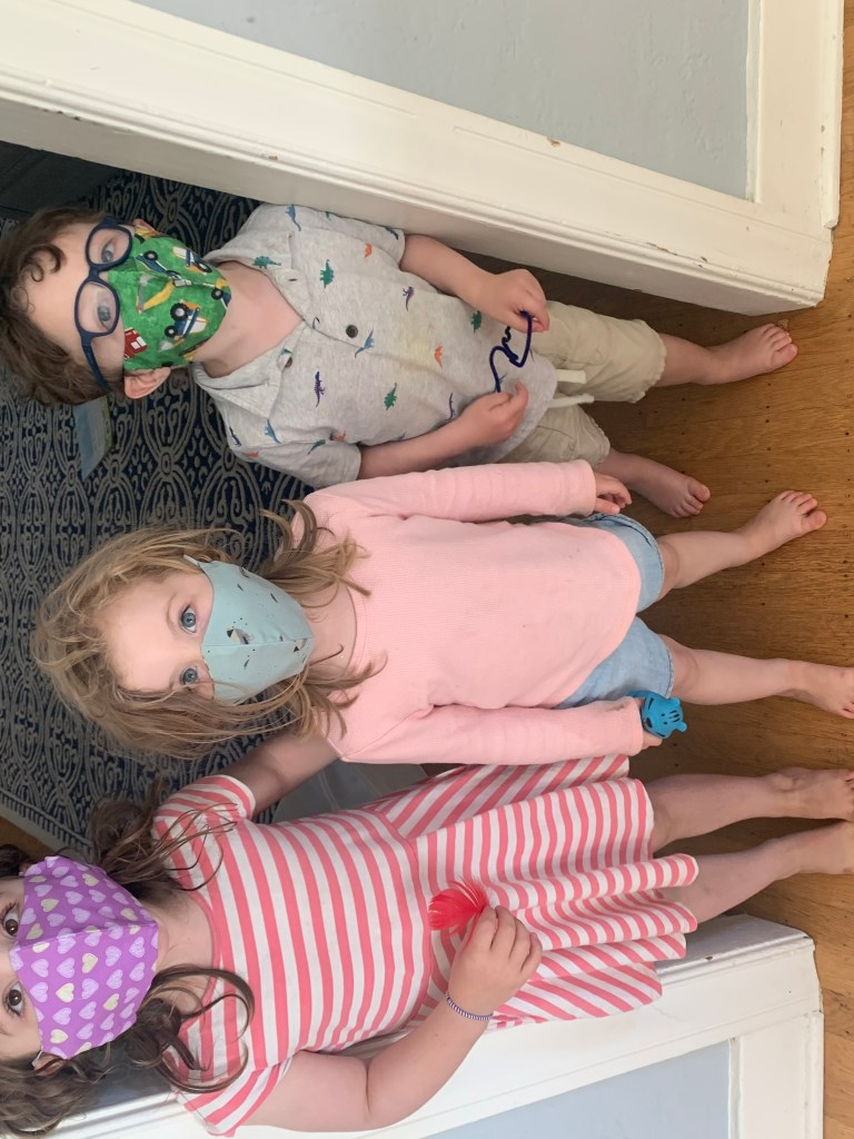 A little girl standing on the left in a doorway wearing a purple cloth face mask peppered with hearts design and looking up. Her younger sister stands next to her left side, wearing a light blue cloth face mask, looks straight ahead. On the other side of the doorframe stands their young brother, wearing a green cloth face mask with a construction vehicle design, looking off to his left.