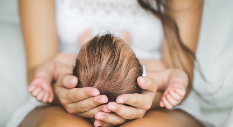 baby held in mother's hands in lap