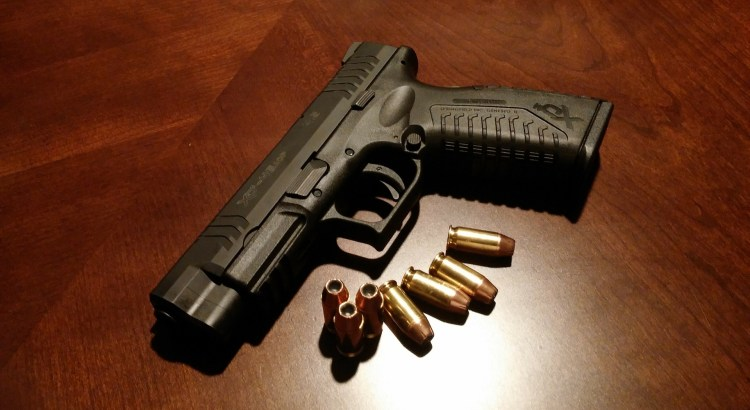 image of a handgun with several bullets