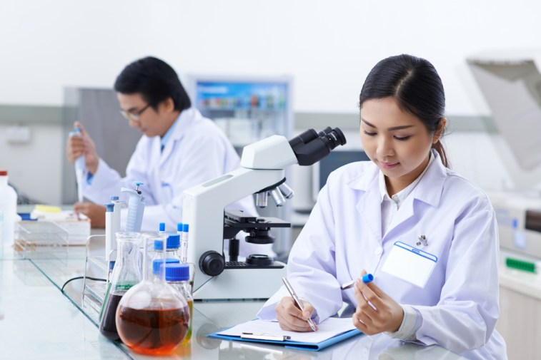 man and woman in a lab consulting blood samples under a microscope