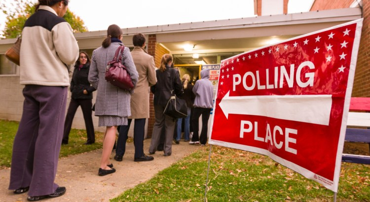 """line of voters in front of a sign that says 'polling place"""""""